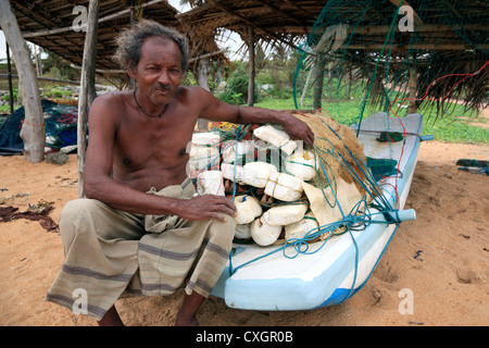 Local fisherman sitting on his boat with his fishing nets piled on top, Waikkal, Sri Lanka - Stock Photo