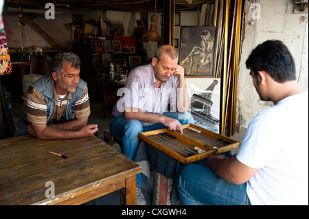 Tavla (Backgammon) players in an antique shop in the old town of Ankara below the citadel, Turkey, with man watching - Stock Photo