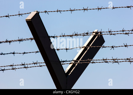 Barbed wire, to protected an area. Iron, metal fence with razor wire on top. - Stock Photo