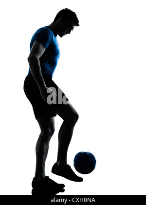 one caucasian man playing soccer juggling football player silhouette  in studio isolated on white background - Stock Photo