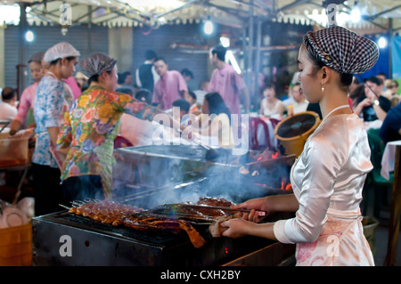 Girl grilling seafood at a restaurant at Ben Thanh night market, Ho Chi Minh City. - Stock Photo