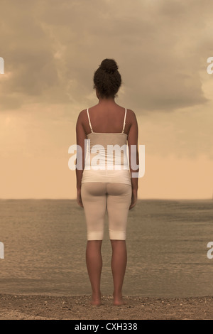 a woman is standing in white sports clothes on the shore of a lake - Stock Photo