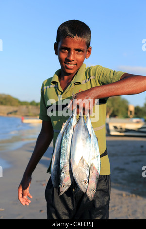 Sri Lankan boy holding freshly caught fish on Back Bay beach in Trincomalee, Sri Lanka. - Stock Photo