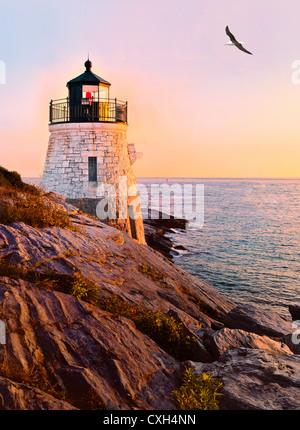 Herring gull laurus flies over Castle Hill lighthouse at twilight sunset over Narragansett Bay Newport Rhode Island - Stock Photo
