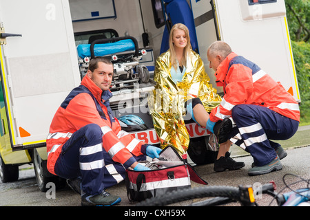 Bike accident woman emergency doctor checking leg in ambulance - Stock Photo