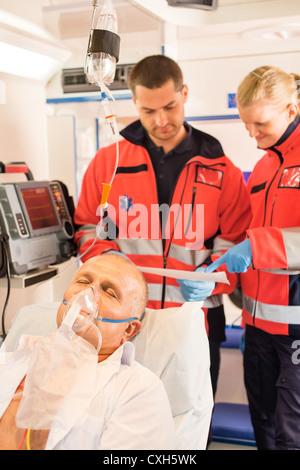Paramedics reading EKG in ambulance patient help emergency woman man - Stock Photo