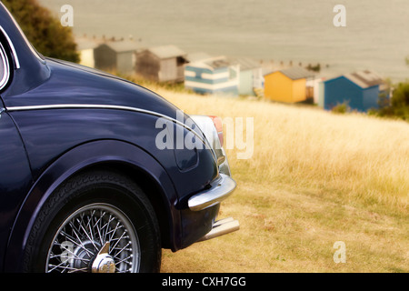 Jaguar Mk II, parked on grass at top of Tankerton slopes, Whitstable, Kent, England, UK with beach huts and sea - Stock Photo