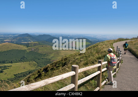 Hiker looking at the view from the Puy-de-Dome onto the volcanic landscape of the Chaine des Puys, Auvergne, France. - Stock Photo
