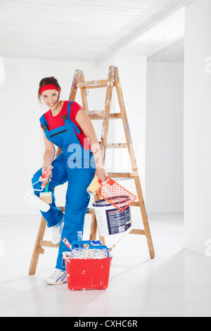Germany, Bavaria, Young woman leaning on step ladder with paint equipments, smiling, portrait - Stock Photo