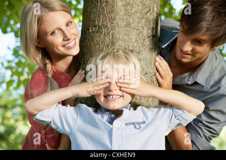 Germany, Cologne, Boy playing hide and seek with parents - Stock Photo