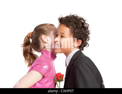 Cute little girl kissing a boy - Stock Photo