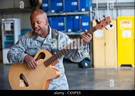 Senior Airman Henry Roberson plays the guitar during a U.S. Air Forces Central Band 'Top Flight' performance at - Stock Photo
