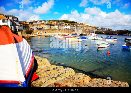 Mousehole Cornwall small fishing village boats in harbour harbor walls moored up waiting for full tide - Stock Photo