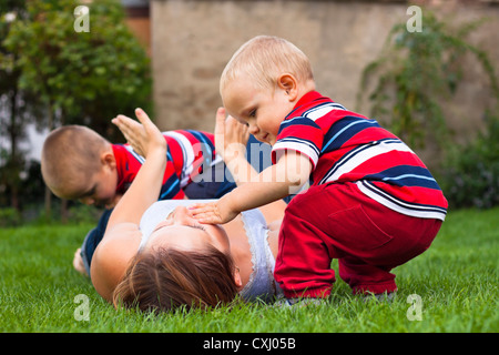 Young happy woman lying on grass playing with children outdoors. - Stock Photo