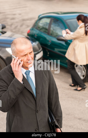 Man on the phone after colliding car woman accident crash - Stock Photo