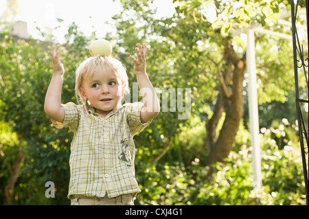 Germany, Bavaria, Boy playing with apple on top of head - Stock Photo