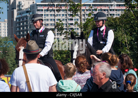 London 2012 Paralympics , Olympic Park Stratford , two mounted policemen police men male cops on horses help crowd - Stock Photo