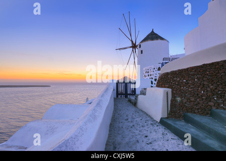 Greece, View of Oia village with traditional Greek windmills in sunset at Santorini - Stock Photo
