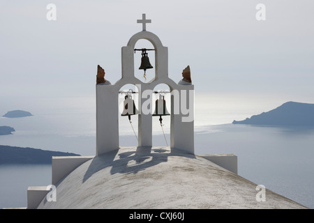 Greece, Bell tower of whitewashed church in Imerovigli, sea in background at Santorini - Stock Photo