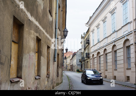 Modern car in narrow paved street - Stock Photo