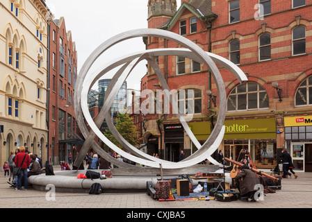 Street scene by Spirit of Belfast steel sculpture by Dan George, nicknamed Onion Rings in Arthur Square Belfast - Stock Photo