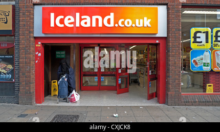 A Muslim woman in a burkha with shopping trolley standing outside the Iceland store Walthamstow High Street London - Stock Photo