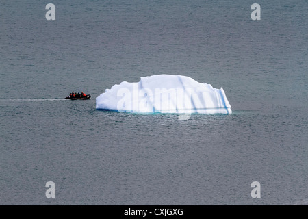 Zodiac boat with tourists coasts by small iceberg in Nunavut, Canada. Summer, high arctic. - Stock Photo