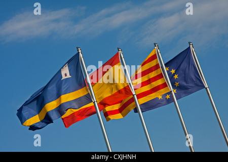 Flags of Salou, Catalonia, Spain, European Union being flown on flagpoles - Stock Photo