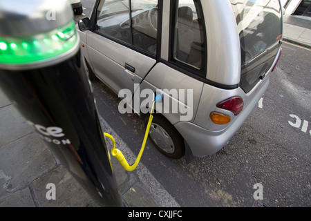 g-whiz Electric car at charging point in London; with charge point operated by Source London UK - Stock Photo