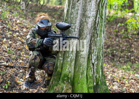 Girl in camo taking cover behind a tree during a paintball tournament. - Stock Photo