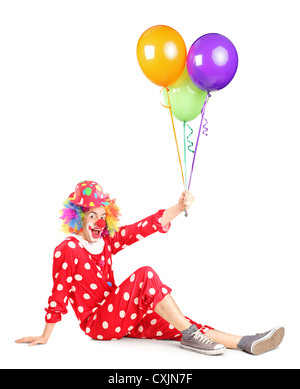 Smiling clown sitting and holding balloons isolated on white background - Stock Photo