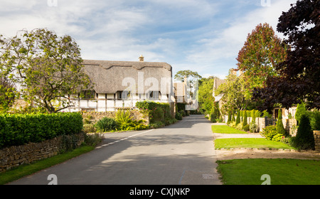 Main street of Stanton with thatched cottages in English Cotswolds - Stock Photo