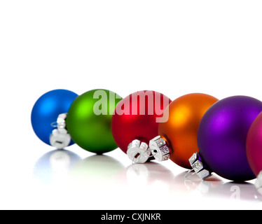 a row of assorted Christmas ornaments/baubles including pink, purple, orange, red, green and blue on a white background - Stock Photo