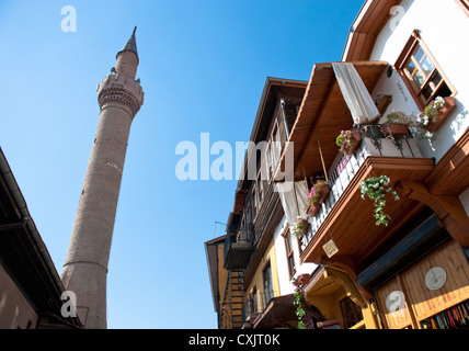 Minarett of a mosque and traditional houses in the old town of Ankara, capital of Turkey - Stock Photo
