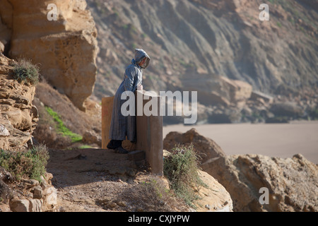 Local Moroccan man in kaftan looking out to sea from the cliff side, Imsouane, Morocco - Stock Photo