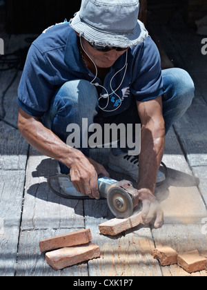 Builder using a hand powered angle grinder to cut bricks. Thailand S.E. Asia - Stock Photo