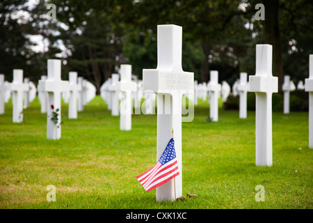Gravestone with American flag at the Normandy American Cemetery at Colleville-sur-Mer, Normandy, France - Stock Photo