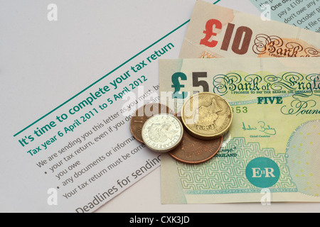 British currency (notes and coins) lying on a letter from the Inland Revenue (tax office) reminding that it's time - Stock Photo