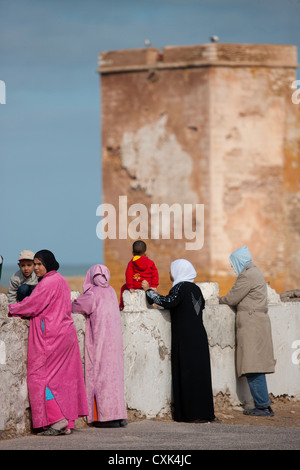 Locals looking at view from city wall in Essaouira, Morocco - Stock Photo