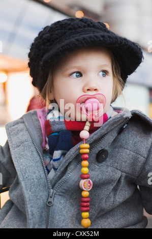 Portrait of Little Girl using Pacifier wearing Winter Cothes - Stock Photo