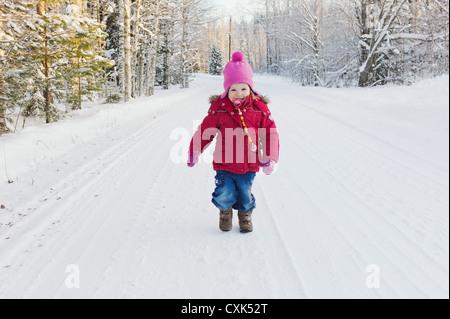 Portrait of Little Girl Walking Down Road in Winter - Stock Photo