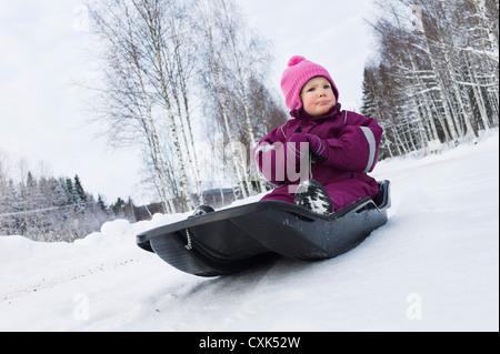 Little Girl on Sled in Winter - Stock Photo