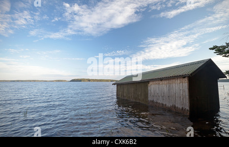 Small wooden boat garage on the coast of Saimaa lake, typically construction for Finland - Stock Photo