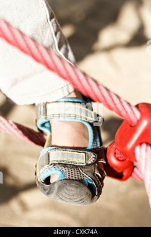 Boy's (6-7) leg on red rope, France. - Stock Photo