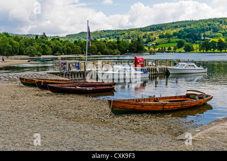 A young girl standing by rowing boats on the scenic shingle beach throws pebbles into the tranquil Coniston Water - Stock Photo