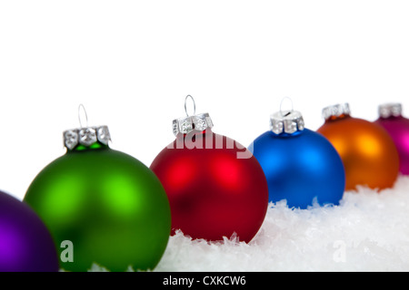 Christmas ornaments/baubles including purple, green, red, blue, orange and pink on a white background with copy - Stock Photo
