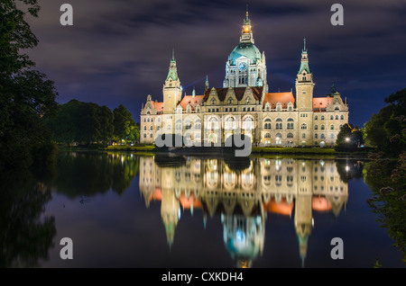 City Hall (Rathaus) of Hannover, Germany by night with cloudy sky and reflection in a lake - Stock Photo