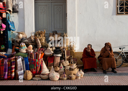 Two Moroccan men sitting outside by shop selling baskets, cloths and souvenirs in Essaouira, Morocco - Stock Photo