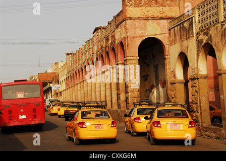 Eritrea, Asmara, cabs and bus on street by an arched building - Stock Photo