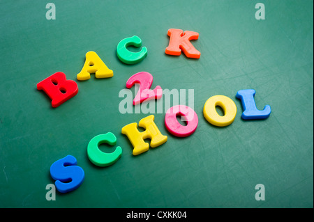 Magnetic alphabet letters on a green chalkboard spelling out Back to School - Stock Photo